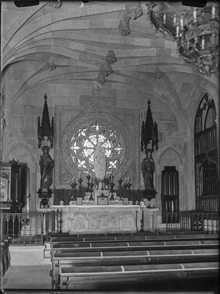 Capilla del palacio de la Sisla con escultura central de la Virgen con el Niño sobre el altar delante del rosetón. Bancos dispuestos para los oficios religiosos. Wunderlich, Otto (1886-1975)